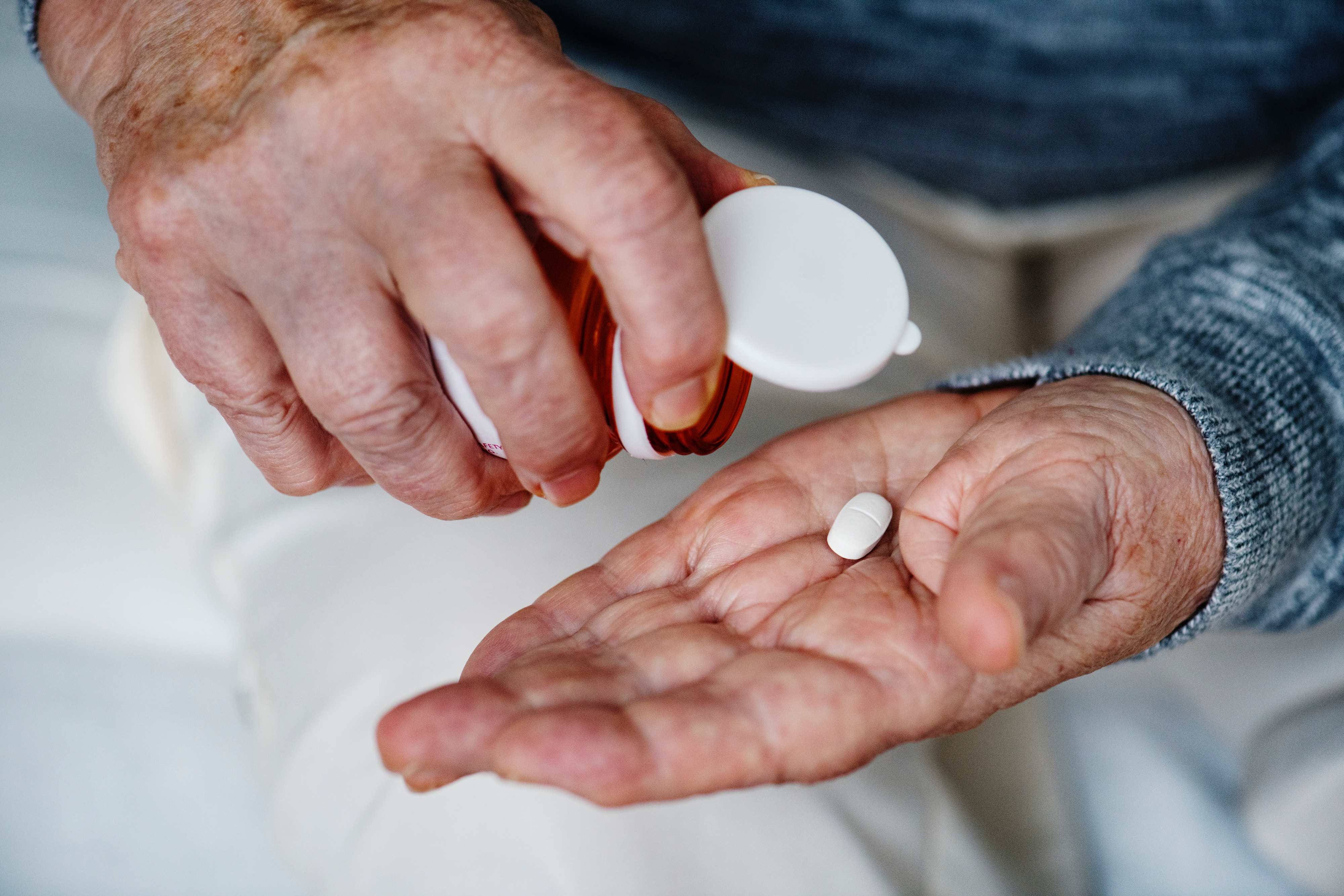 Middle aged hands pouring pill into hand from bottle.